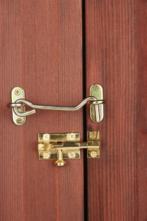 Metal hook and deadbolt in wooden door close-up photo