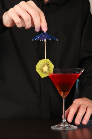 Bartender making and decorating cocktail on close-up photo