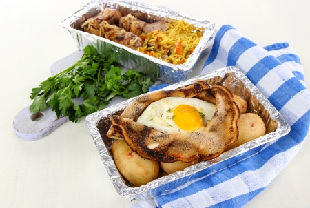 Food in boxes of foil on napkin on wooden board isolated in white photo