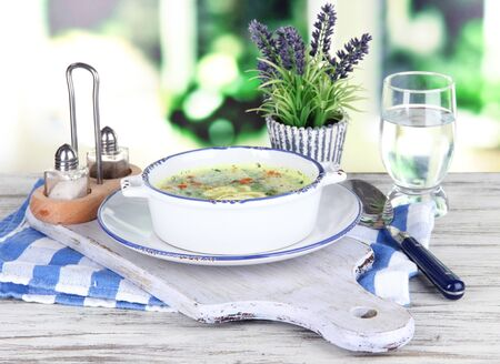 Soup in plate on napkin on wooden board on window background Stock Photo - 21704637