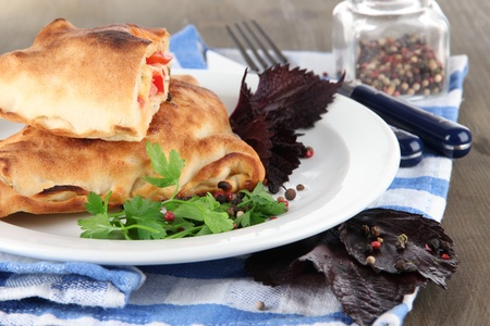 Pizza calzones on plate on napkin on wooden table  photo