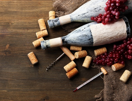 Old bottles of wine, grapes and corks on wooden background photo