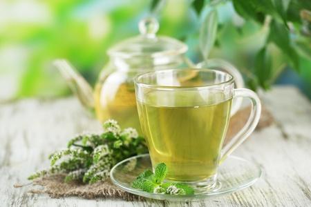 teepflanze: Teekanne und Tasse Kr�utertee mit frischer Minze Blumen auf Holztisch Lizenzfreie Bilder