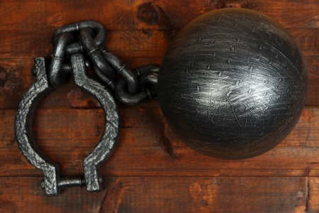 Ball and chain on wooden background photo