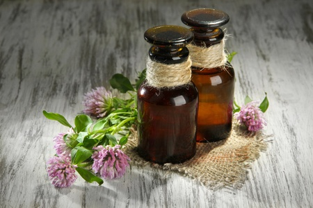 Medicine bottles with clover flowers on wooden table photo