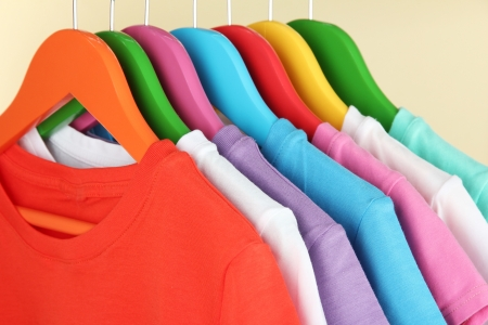 Different shirts on colorful hangers on beige background photo