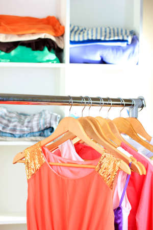 Variety of clothes on wooden hangers on shelves background photo