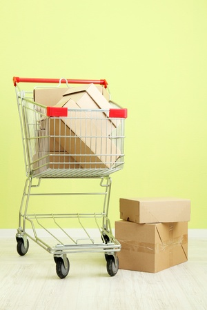 Shopping cart with carton, on green wall background photo