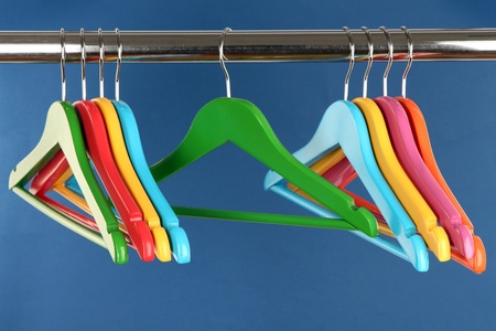 Colorful clothes hangers on blue background photo