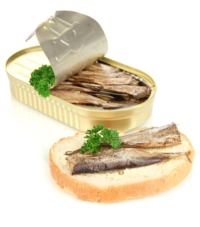 Open tin can with sardines and tasty sandwich, isolated on white photo