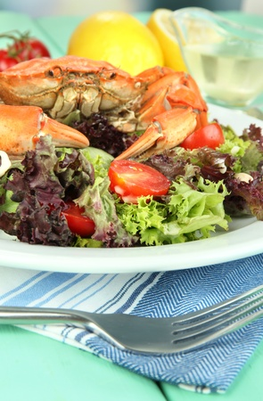 Boiled crab on white plate with salad leaves and tomatoes,on wooden table background photo
