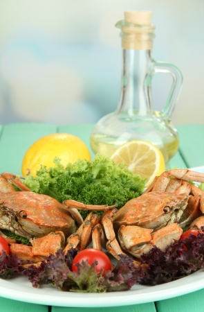 Boiled crabs on white plate with salad leaves and tomatoes,on wooden table, on bright background photo