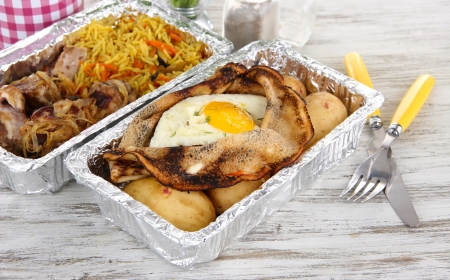 Food in boxes of foil on wooden table photo