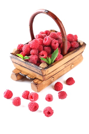 Ripe sweet raspberries in wooden basket, isolated on white photo