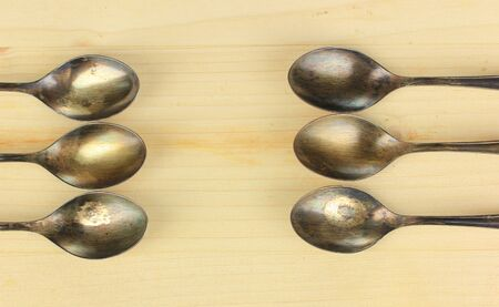 Vintage metal spoons on wooden table close-up photo