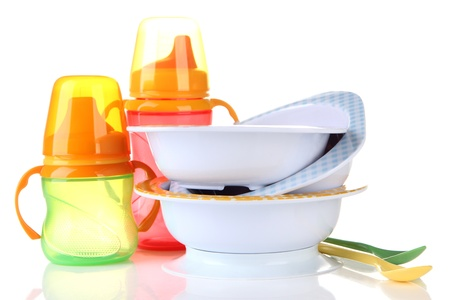 Bright baby bottles, bowls and spoons isolated on white