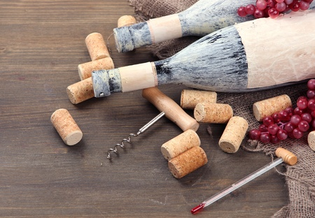dusty: Old bottles of wine, grapes and corks on wooden background Stock Photo