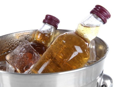 Minibar bottles in bucket with ice cubes, isolated on white photo