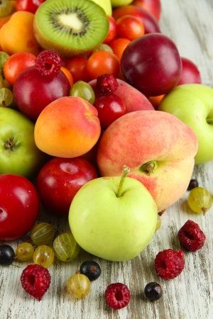 Assortment of juicy fruits, on wooden background photo