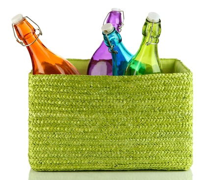 Color glass bottles in  color wicker basket, isolated on white photo