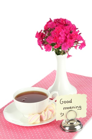 Beautiful bouquet of phlox with cup of tea isolated on white photo