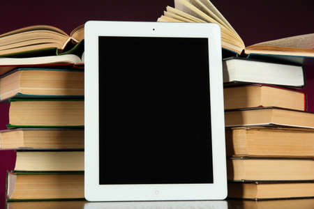 Tablet and books on bright background photo
