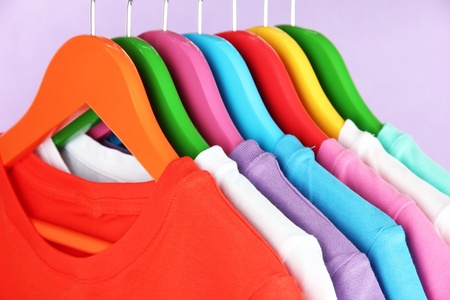 Different shirts on colorful hangers on purple background photo