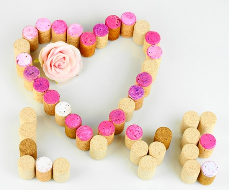 Wine corks laid out in form of heart isolated on white photo