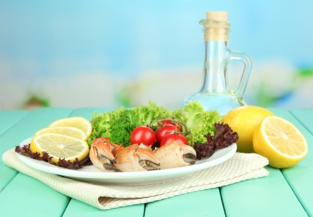Boiled crab claws on white plate with salad leaves and tomatoes,on wooden table, on bright  background photo