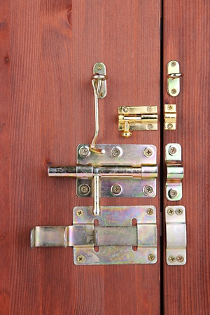 pawl: Metal bolts, latches and hooks in wooden door close-up