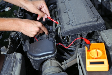 car battery: Auto mechanic uses multimeter voltmeter to check voltage level in car battery