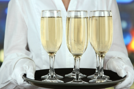 Waitresses holding tray with glasses of champagne photo