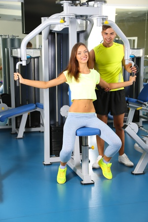 simulator: Girl and trainer engaged in simulator in gym