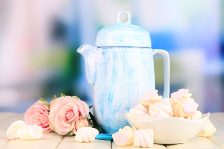 Antique white teapot on wooden table on room background photo