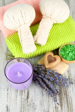 Still life with lavender candle, soap, massage balls, soap and fresh lavender, on wooden background photo