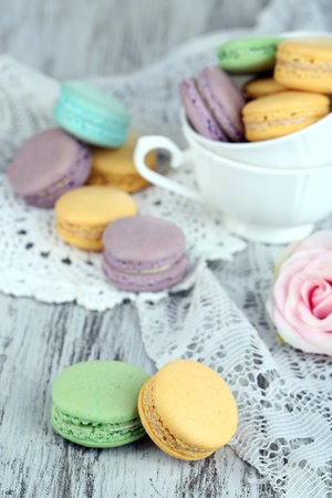 Macaroons in bowl on wooden table close-up photo