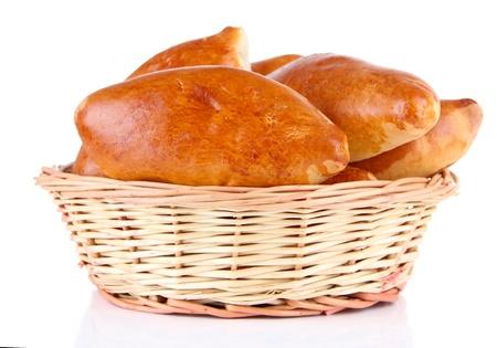 canasta de pan: Empanadas al horno frescos en la cesta de mimbre, aislados en blanco Foto de archivo