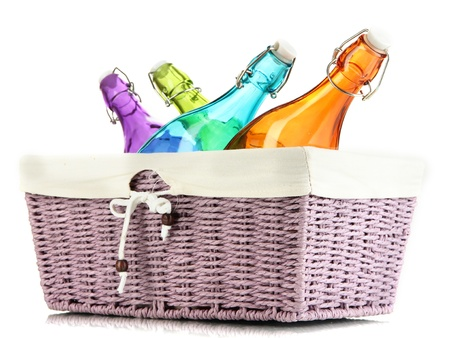 Color glass bottles in wicker basket, isolated on white photo