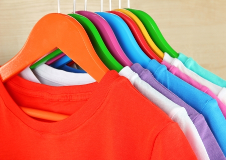 Different shirts on colorful hangers on light background photo