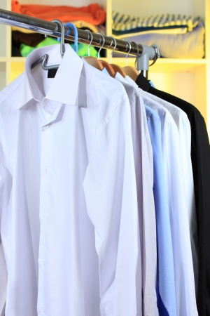 Variety of casual shirts on wooden hangers on shelves background photo