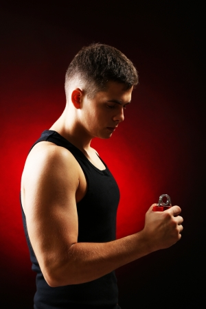Handsome young muscular sportsman with expander, on dark background photo