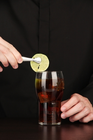 Bartender making cocktail on bright background, close-up photo