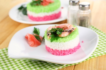 Colored rice on plates on napkin on wooden table Stock Photo - 21865145
