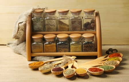 Assortment of spices in wooden spoons and jars, on wooden background