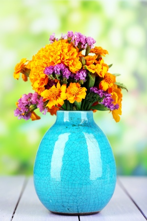 Bouquet of marigold flowers in vase on wooden table on natural background photo