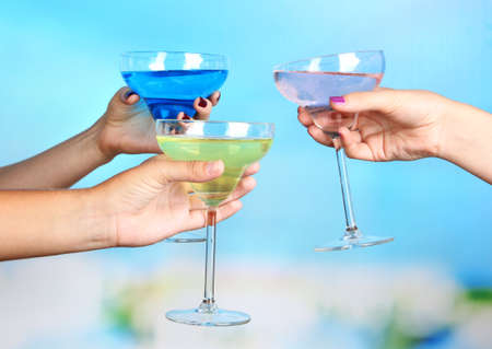 Cocktails in hands on pool background photo