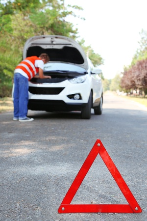 Broken down car with red warning triangle photo