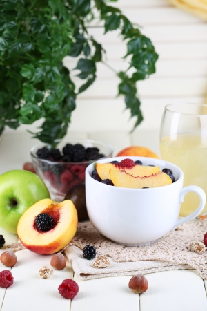 Oatmeal in cup with berries on napkins on wooden table on bright background photo
