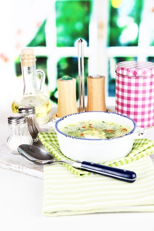 Soup in plate on napkin on wooden board on window background photo