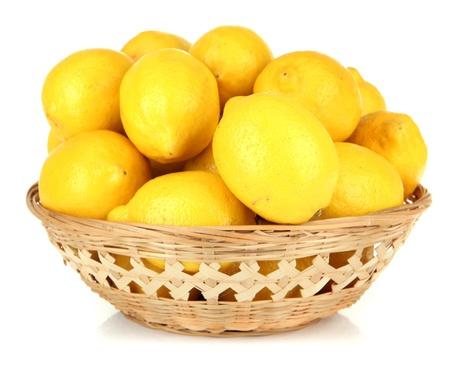 nutriments: Ripe lemons in wicker basket isolated on white Stock Photo